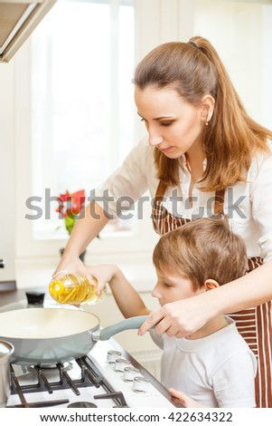 Young woman using pan on cooker together with her son. Family cooking background - stock photo