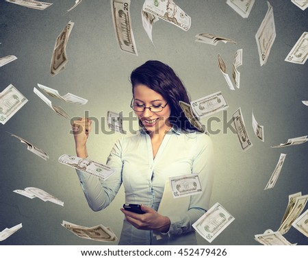Young woman using smart phone building online business making money dollar bills falling down. Beginner IT entrepreneur under cash rain. Success banking economy concept