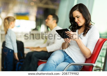 young woman using tablet computer at airport with family on background - stock photo