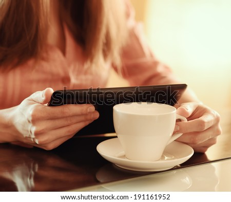 Young woman using tablet computer in cafe.