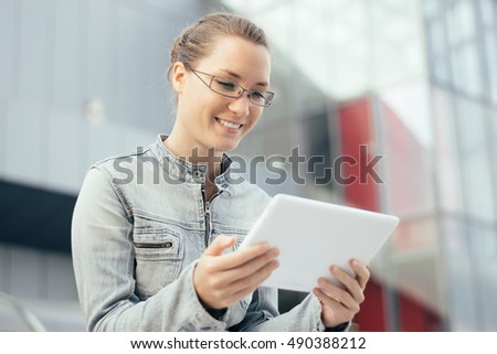 Young woman using tablet computer outdoor in a city