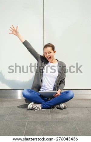 young woman using tablet leaning to wall, very happy emotions - stock photo