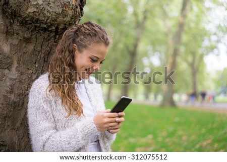 Young woman using tablet & mobile phone in the park