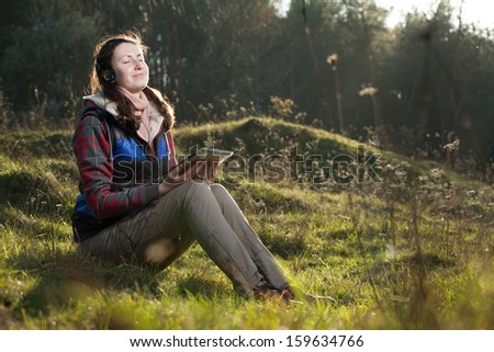 Young woman using tablet outdoor - stock photo