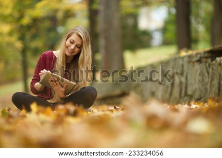 Young woman using tablet outdoor sitting on grass and smiling. Girl using digital tablet pc in the park. Student using tablet after school. - stock photo