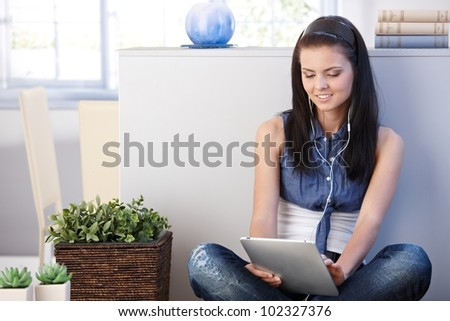 Young woman using tablet, sitting at home, smiling. - stock photo