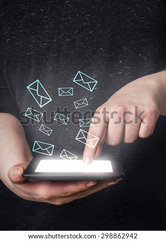 Young woman using tablet with email icons around - stock photo
