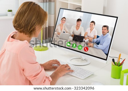 Young Woman Videoconferencing With Colleagues On Computer At Desk - stock photo