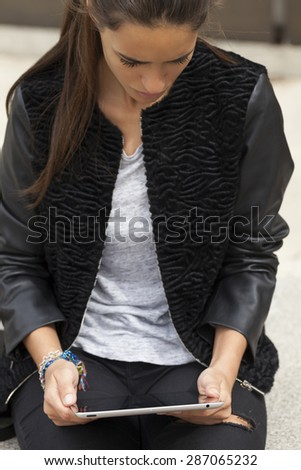 Young woman viewing a tablet seating outdoors in the city.