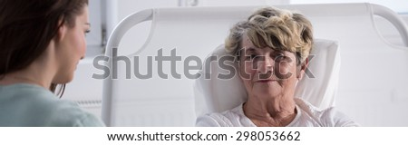 Young woman visiting her sick grandmother at hospice - stock photo
