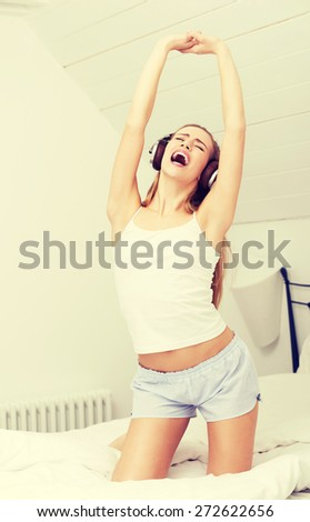 Young woman waking up and yawning - stock photo