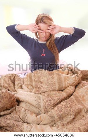Young woman waking up in her bed - stock photo