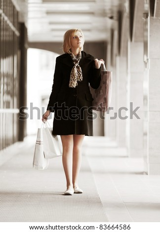 Young woman walking against a shopping mall