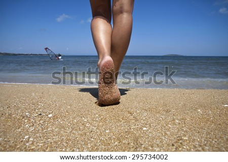 Young woman walking alone on sand beach. Closeup detail of female feet and golden sand.