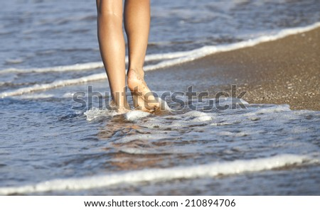 Young woman walking alone on the sand beach in the sunset and the water is lapping at her feet.