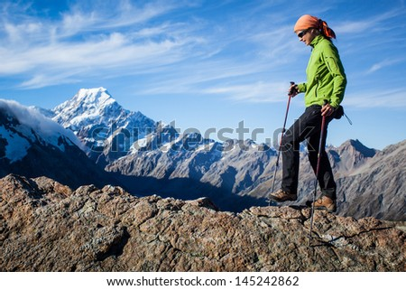 Young woman walking along mountain ridge - stock photo