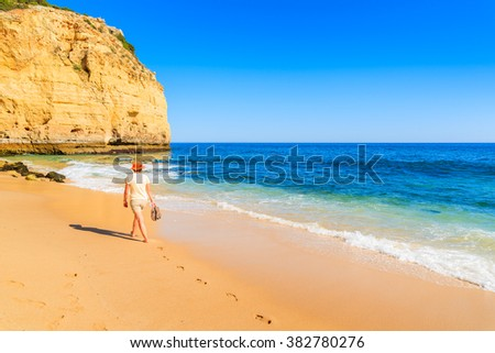 Young woman walking along Vale Centianes beach, Portugal