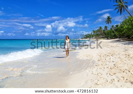 Young woman walking along white sand tropical beach. Beautiful girl in white dress on the beach. Travel and vacation. Freedom concept.
