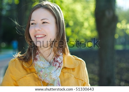 young woman walking and listening music - stock photo
