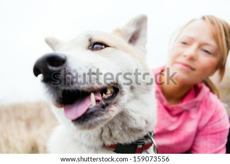 Young woman walking and playing with her akita inu dog in autumn nature outdoors. Beautiful girl and happy dog portrait.