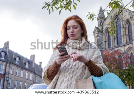 Young woman walking down a high street using her smartphone. She has shopping bags on her arms.  - stock photo