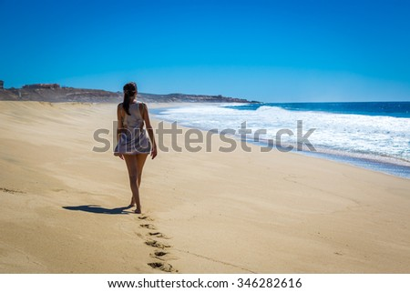 Young woman walking in a empty beach in Mexico