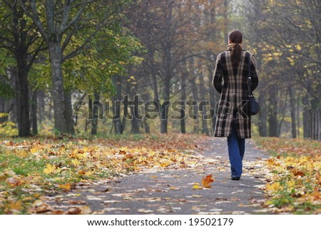 Young woman walking in an autumn park