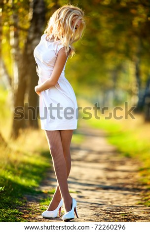 Young woman walking in autumn park. - stock photo