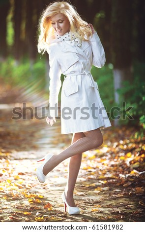 Young woman walking in autumn park. Light shine effect. - stock photo
