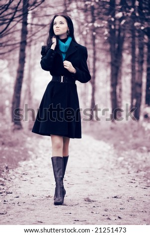 Young woman walking in forest. Soft pink and blue tint. - stock photo