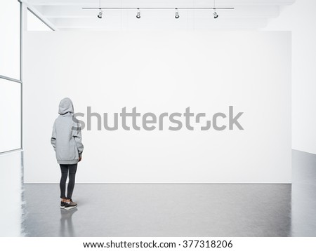 Young woman walking in modern gallery and looking at the blank canvas - stock photo