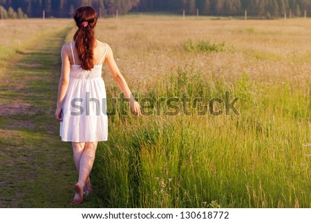 Young woman walking in nature. - stock photo