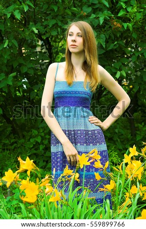 Young woman walking in the blooming garden
