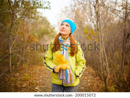 Young woman walking in the fall season. Autumn outdoor portrait. - stock photo