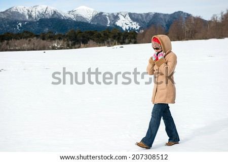 Young woman walking in the snow - stock photo