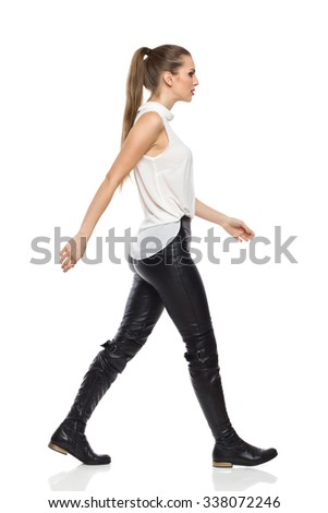 Young woman walking in white shirt and black leather trousers. Side view. Full length studio shot isolated on white. - stock photo
