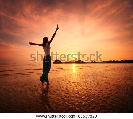 Young woman walking on a sandy beach - stock photo