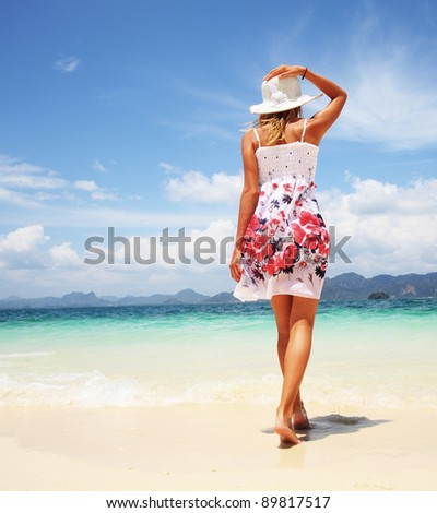 Young woman walking on a warm beach - stock photo