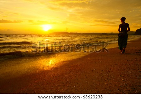 Young woman walking on beach under sunset light - stock photo