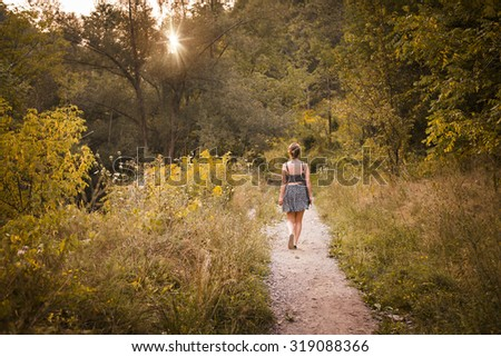 Young woman walking on path in late afternoon summer forest with setting sun