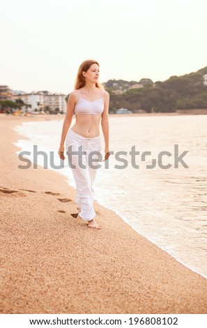 Young woman walking on sea background. - stock photo