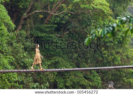 young woman walking on suspended wooden bridge in jungle, Thailand - stock photo