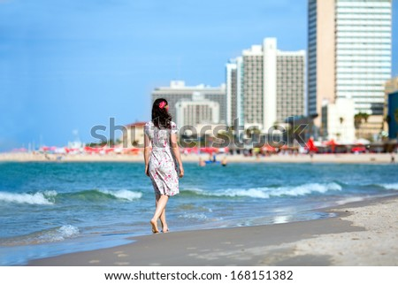 Young woman walking on the beach in Tel-Aviv - stock photo