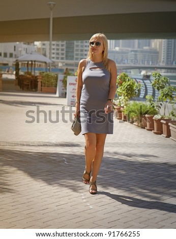 Young woman  walking on the street at summer - stock photo