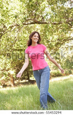 Young Woman Walking Through Long Grass In Park - stock photo