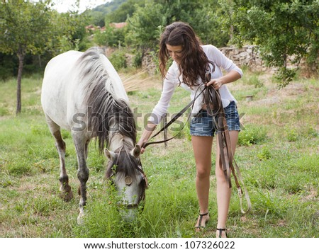 Young woman walking with a farm horse in a meadow - stock photo