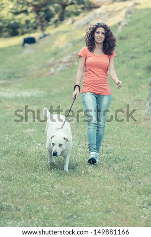 Young Woman Walking with Her Dog - stock photo