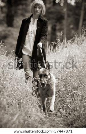 Young woman walking with her dog through the tall grass, light sepia tone,focus on the dog - stock photo