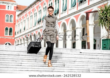 Young woman walking with travel bag down stairs at the Republic square in Split city - stock photo