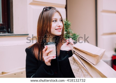 Young woman walks around the city and drinking coffee after shopping. Street style. Film processing